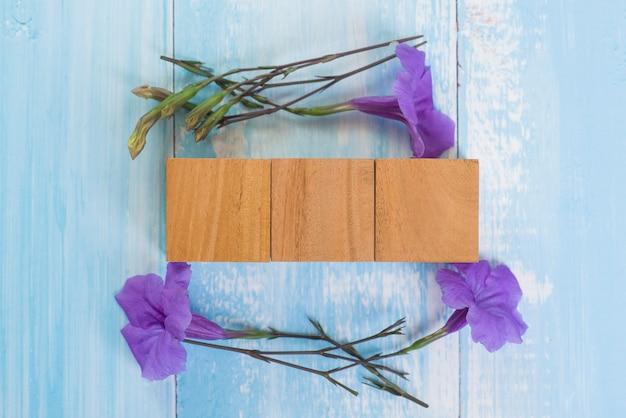 Leerer hölzerner würfelblock mit purpurroter blume