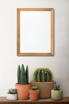 Leerer holzbilderrahmen auf einem regal mit kaktus
