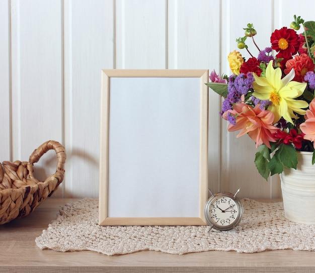 Leerer holzrahmen auf einem tisch mit blumen und einer metalluhr für ihren text oder ein sommermodell in einem rustikalen interieur
