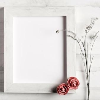 Leerer holzrahmen mit rosen und blumen