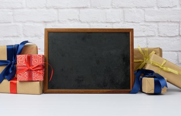 Leerer holzrahmen und stapel verschiedener geschenkboxen auf weißem backsteinhintergrund, festlicher hintergrund