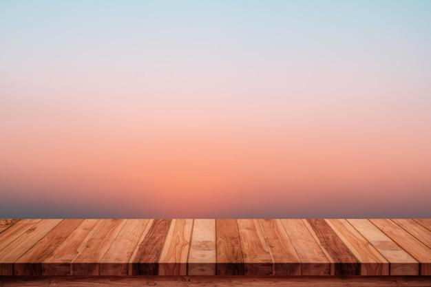 Leerer holztisch mit abstraktem steigungssonnenaufgang im natürlichen hintergrund des himmels.