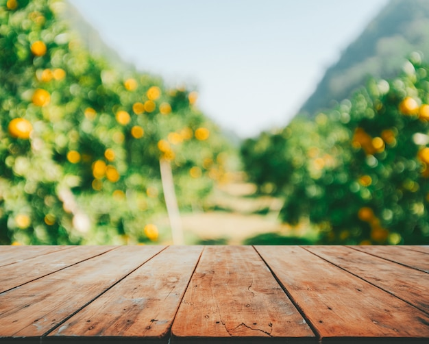 Leerer holztisch mit orangenbäumen