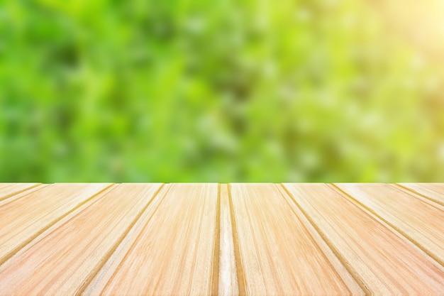 Leerer holztisch mit unscharfem grünem hintergrund. konzeptparty, produkte, frühling