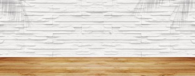 Leerer holztisch mit weißer steinmauer
