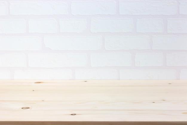 Leerer holztisch über weißer backsteinmauer, schablone