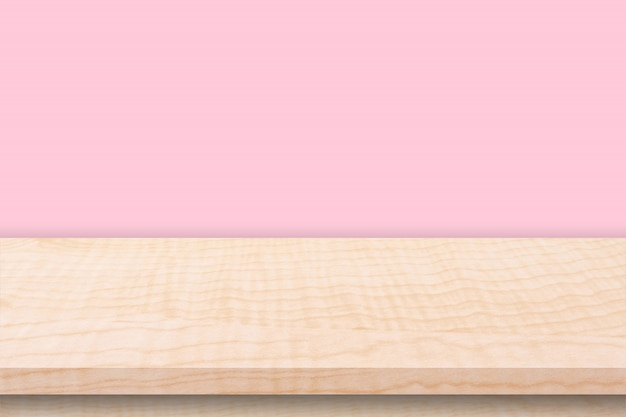Leerer holztisch und rosa wandhintergrundbeschaffenheit, anzeigenmontage mit kopienraum.