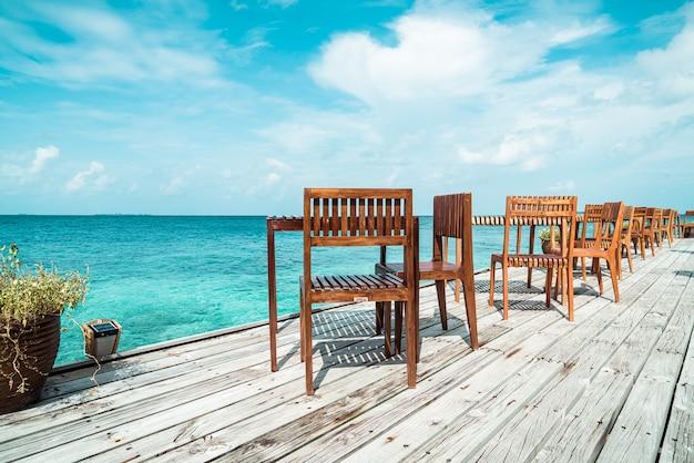 Leerer holztisch und stuhl im freien mit meerblickhintergrund auf den malediven