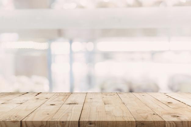 Leerer holztisch und unscharfer hintergrund - speicher des einkaufszentrums verwischen hintergrund bokeh mit anzeigenmontage für produkt.