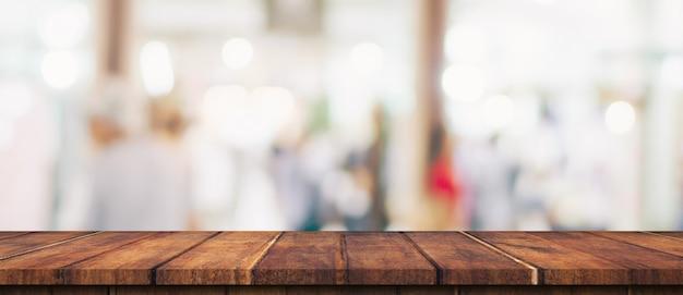 Leerer holztisch und unscharfer leuchttisch im einkaufszentrum mit bokeh-hintergrund. produktanzeigevorlage.