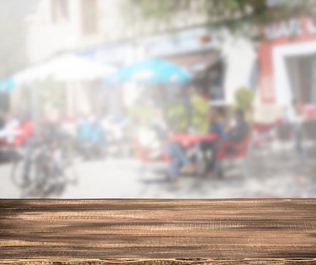 Leerer holztisch und verschwommener café-hintergrund, produktpräsentation
