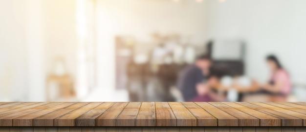 Leerer holztisch und verschwommener leuchttisch im café und café mit bokeh