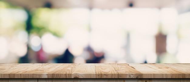 Leerer holztisch und verschwommener lichttisch im café und café mit bokeh-hintergrund. vorlage für die produktanzeige.