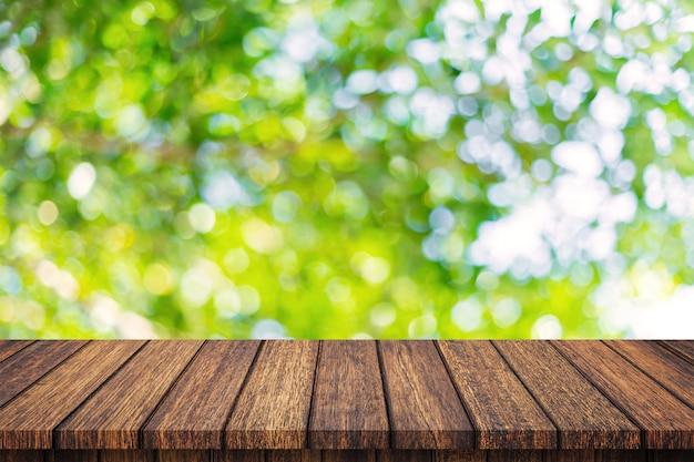 Leerer holztisch und zusammenfassung unscharfes grünes bokeh lässt hintergrundbeschaffenheit, anzeigenmontage mit kopienraum.