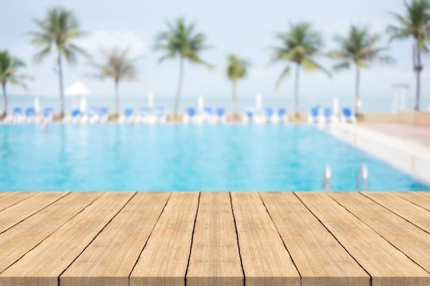 Leerer holztisch vor mit unscharfem hintergrund des swimmingpools am strand