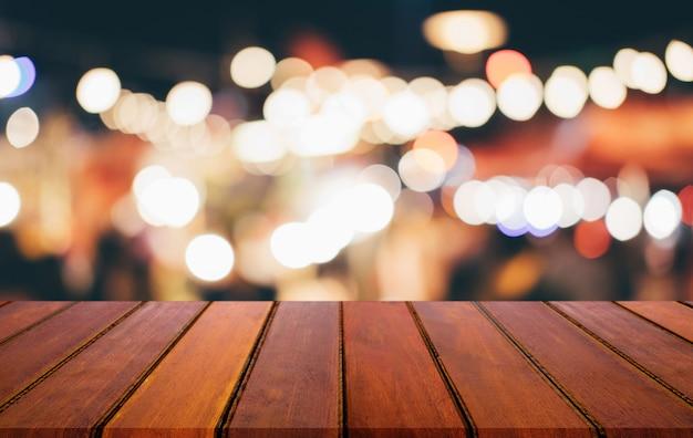 Leerer holztisch vor zusammenfassung unscharfem festlichem hellem hintergrund mit hellen stellen und bokeh