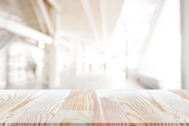 Leerer kiefernholztisch auf die oberseite über unschärfehintergrund, kann benutzter spott oben sein.
