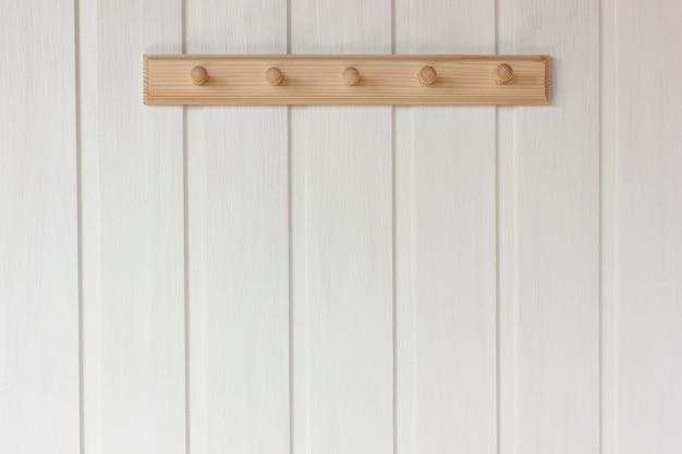 Leerer kleiderbügel des natürlichen holzes auf einer weißen wand. rustikales interieur als hintergrund, kopierraum.