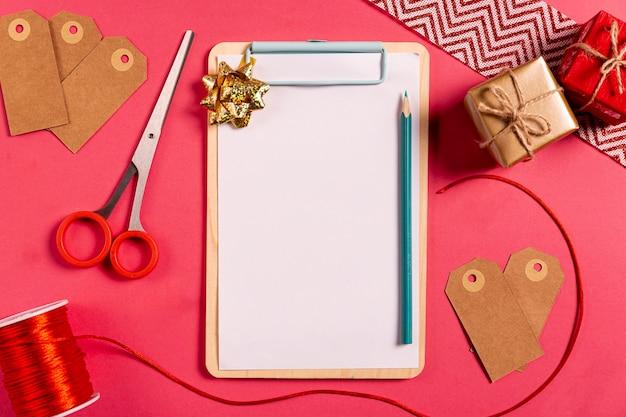 Leerer klemmbrettbleistift und kleine geschenke