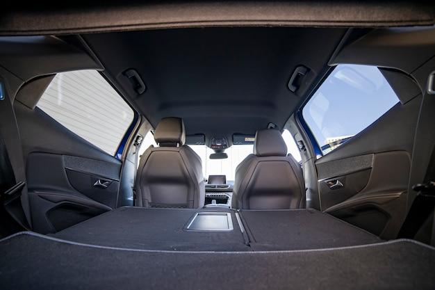 Leerer kofferraum eines modernen autos mit umgeklappten rücksitzen. großes innenvolumen. kofferraumansicht