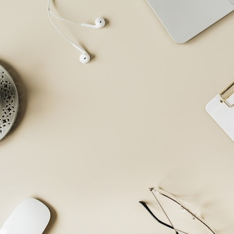 Leerer kopierraum des runden rahmens verspotten arbeitsbereich des home-office-schreibtisches mit laptop, zwischenablage, kopfhörern, kaffee auf beige