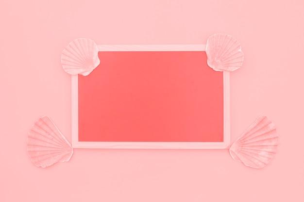 Leerer korallenroter rahmen verziert mit muschelschalen auf rosa hintergrund