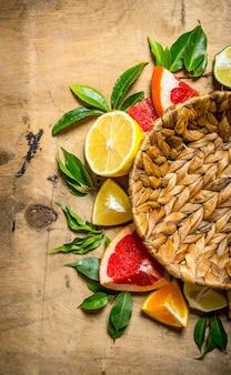 Leerer korb und grapefruit, orange, mandarine, zitrone, limette mit blättern auf holztisch. draufsicht