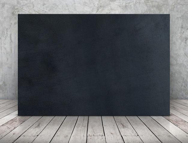 Leerer langer schwarzer gewebesegeltuchrahmen, der an der betonmauer auf hölzernem plankenboden sich lehnt