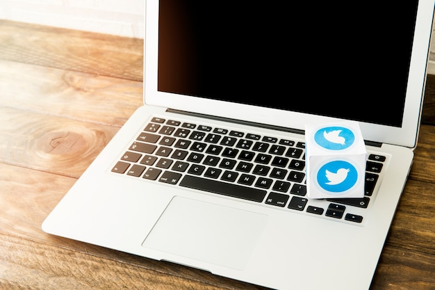 Leerer laptop mit kasten der twitterikone auf schreibtisch