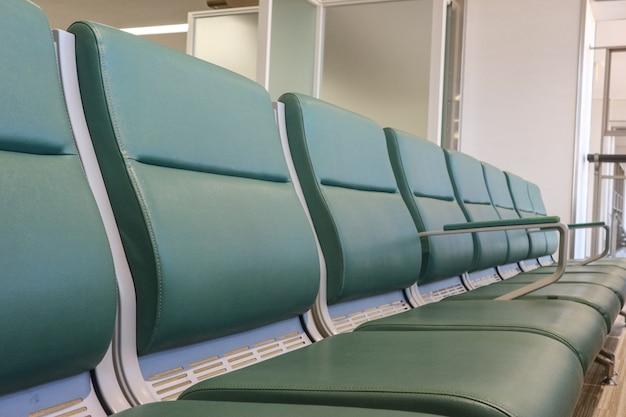 Leerer ledersitz zum warten auf das einsteigen in die zone des flughafen-endbereichs.
