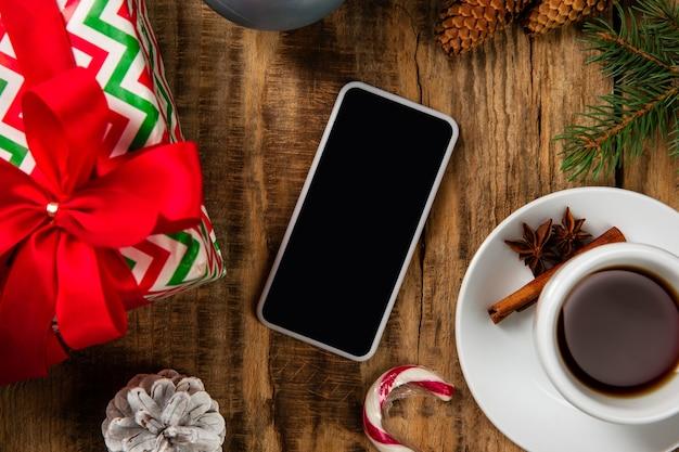 Leerer leerer bildschirm des smartphones an der holzwand mit bunter feiertagsdekoration, tee und geschenken.