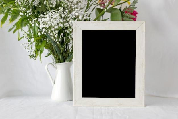 Leerer leerer fotorahmen mit blumenvase auf weißer tabelle