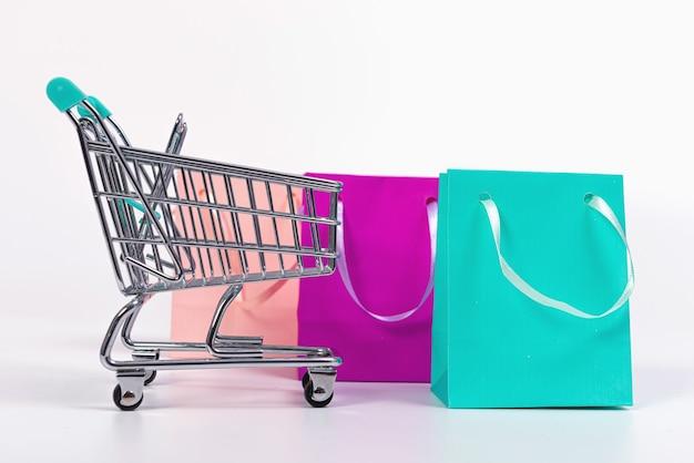 Leerer mini-einkaufswagen und bunte papiertüten lokalisiert auf heller oberfläche, modell für design