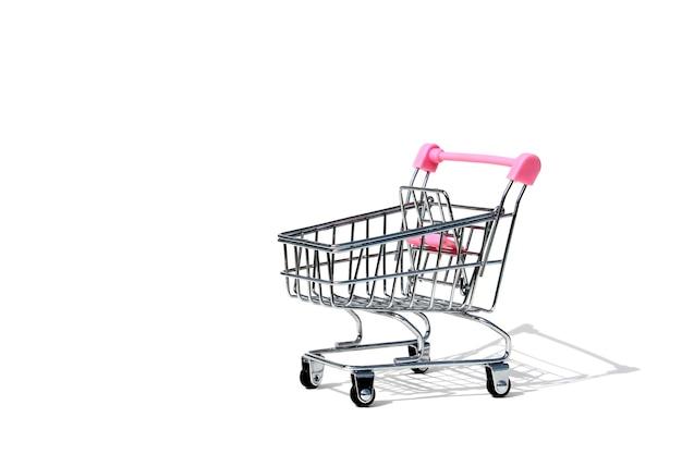 Leerer miniatur-eiseneinkaufswagen im supermarkt lokalisiert auf weißer wand. handels- und geschäftsthema mit platz für text