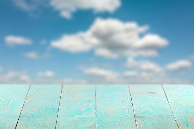 Leerer natürlicher hölzerner blauer tisch gegen unscharfen hintergrund des blauen bewölkten himmels für gegenwärtiges produkt und andere dinge, kopienraum. kann für ihre kreativität verwendet werden.