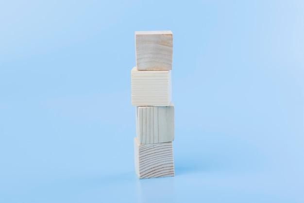 Leerer natürlicher hölzerner würfelblock auf blauem hintergrund