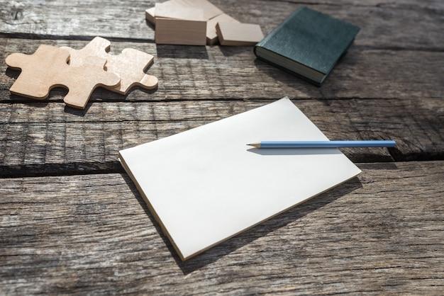 Leerer notizblock auf einem rustikalen holzschreibtisch mit bleistift darauf und holzpuzzles und blöcken