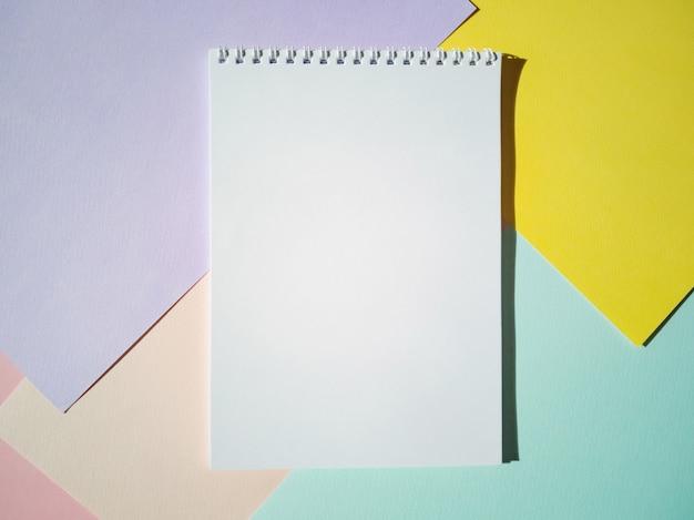 Leerer notizblock auf einer spirale mit weißen seiten auf farbigen blättern papier. draufsicht, minimalismus, flache lage.