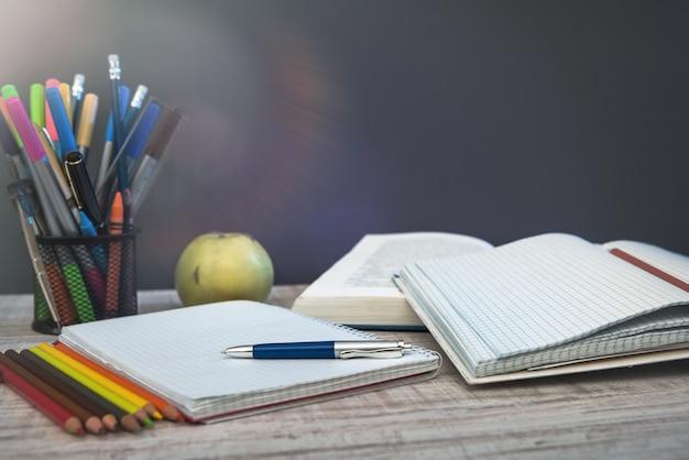 Leerer notizblock auf lehrertisch gegen tafel. bildungskonzept.