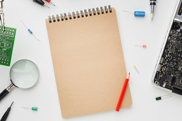 Leerer notizblock der draufsicht mit laptop