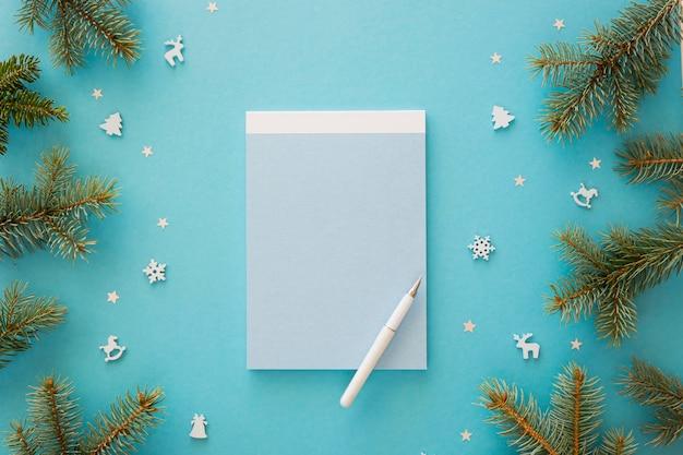 Leerer notizblock der draufsicht, umgeben von weihnachtselementen