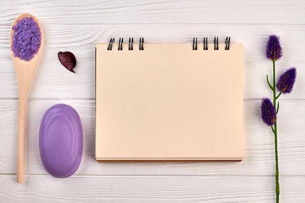 Leerer notizblock für exemplar und spa-zubehör. lila seife mit salz und lavendel auf weißem schreibtisch aus holz.