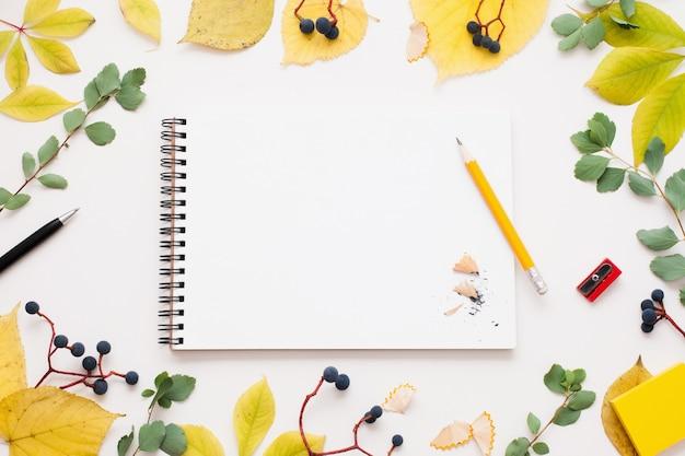 Leerer notizblock im herbstlaubrahmen