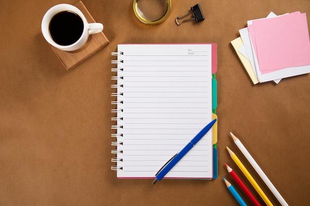 Leerer notizblock mit büromaterial und kaffee auf dem tisch
