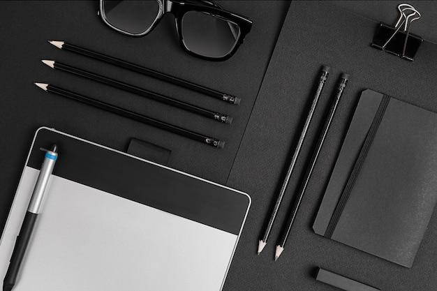 Leerer notizblock mit clips, stiften und gläsern flach liegen. draufsicht auf satz schwarzer büromaterialien und brillen, freier raum.