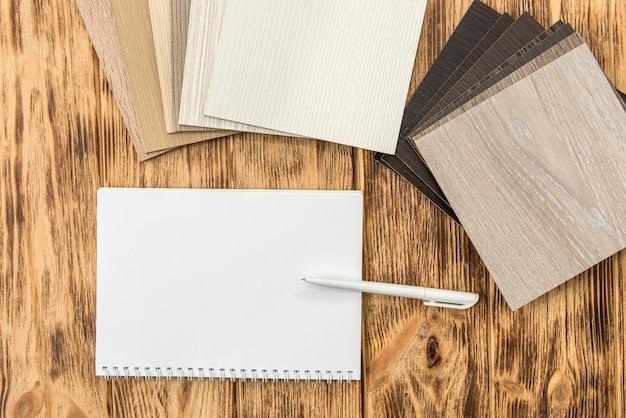 Leerer notizblock mit holzbodenkatalog für neues design ihres hauses. plankenlaminatkollektion für innendekoration
