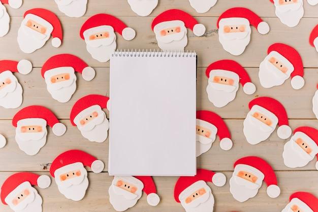 Leerer notizblock mit kleinen santa clauses