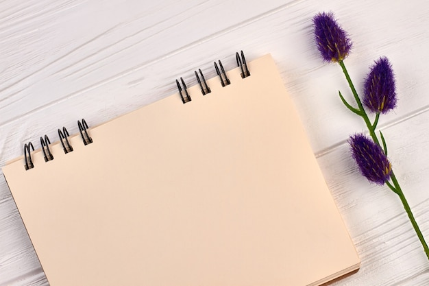 Leerer notizblock mit lavendel auf weißem schreibtisch aus holz.