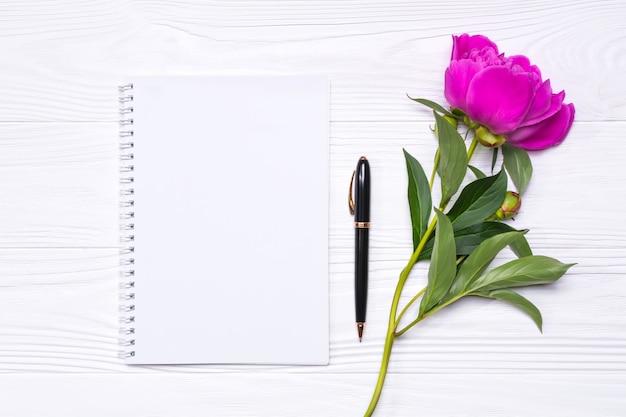 Leerer notizblock mit platz für text, stift und pfingstrosenblume auf einem weißen hölzernen hintergrund