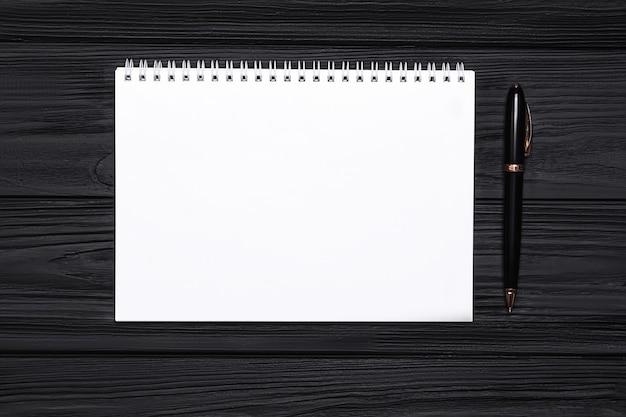 Leerer notizblock mit platz für text und stift auf schwarz